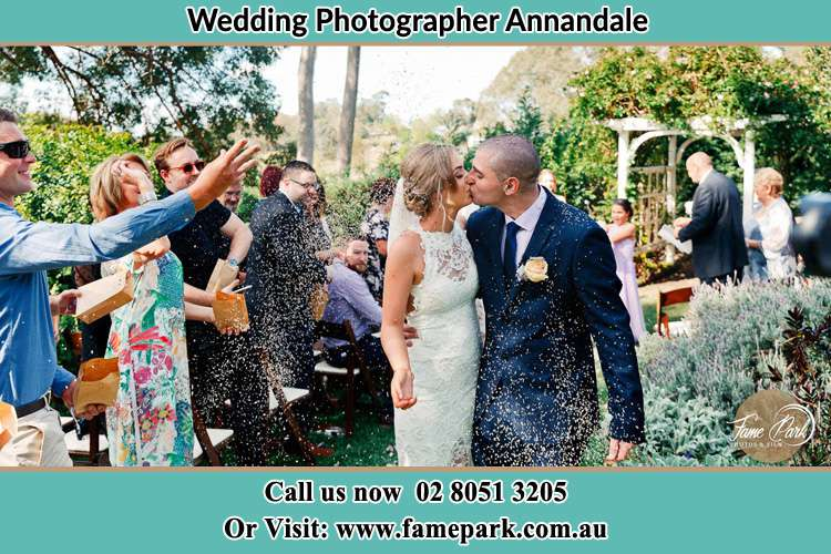 Photo of the Bride and the Groom kissing while showering rice by the visitors Annandale NSW 2038