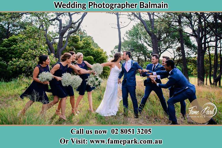 Photo of the Bride and the Groom kissing while teasing by the entourage Balmain NSW 2041