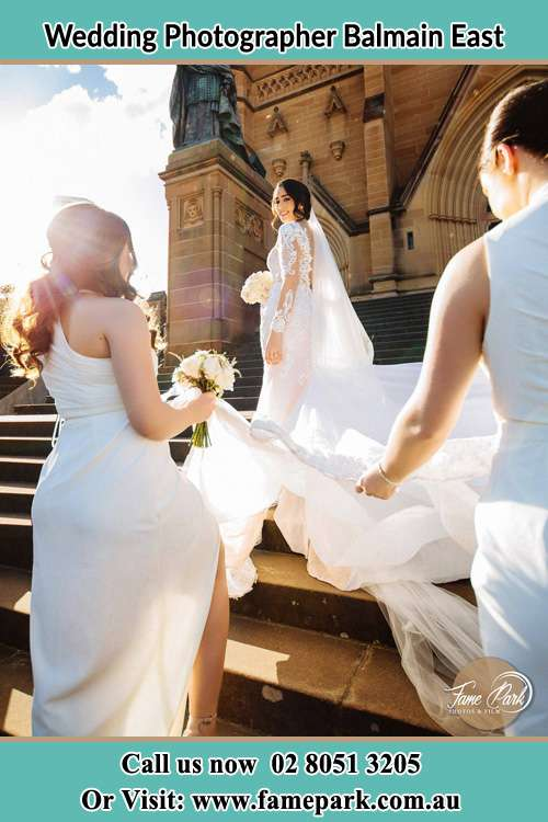 Photo of the Bride smiling on the bridesmaid holding the tail of her wedding gown at the front of the church Balmain East NSW 2041